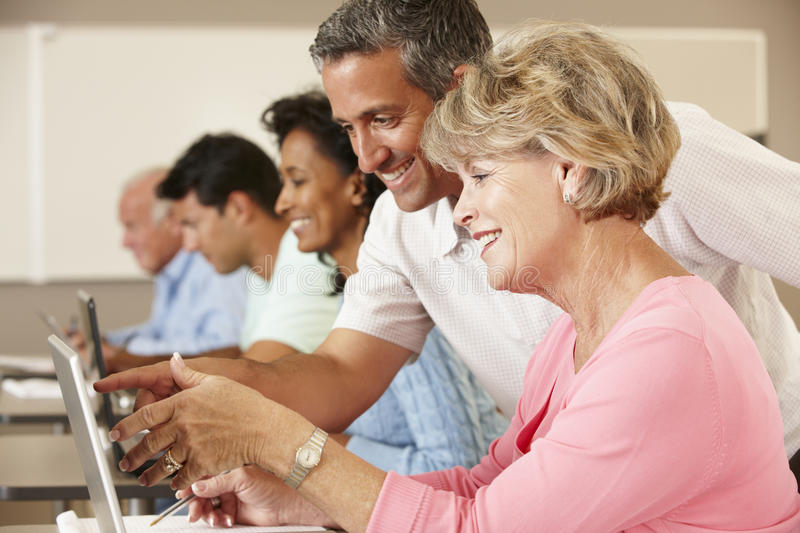 Teacher and mature students in class stock image