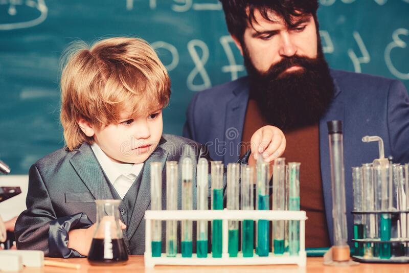 Teacher man with little boy. Biology Science lab. father and son at school. learning chemistry in school laboratory stock image