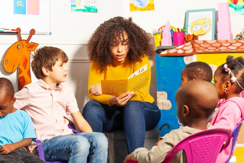 Teacher in nursery school reading a book to kids stock photography