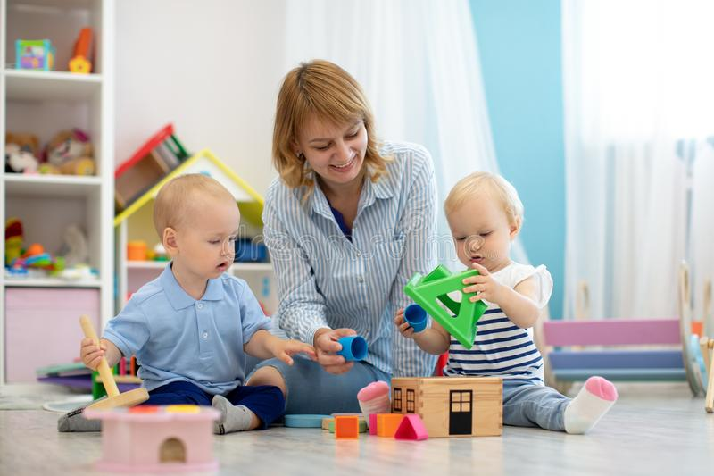 Mentor and 1 years old babies playing with educational toys in kindergarten royalty free stock photo