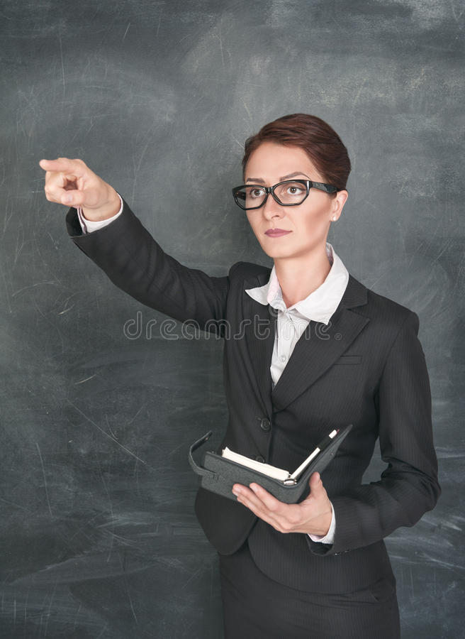 Teacher with organizer pointing on someone. Woman teacher in glasses with organizer pointing on someone stock images