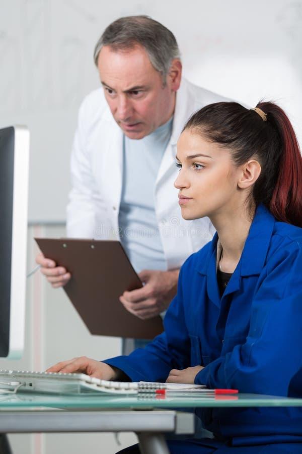 Teacher overseeing student working on computer stock photo