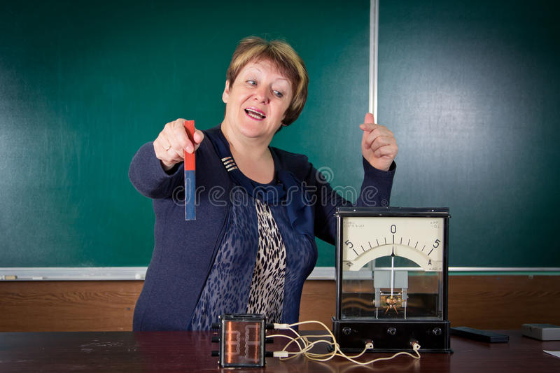The teacher of physics explains concept of electromagnetic induction. Electrical engineering bases royalty free stock photos