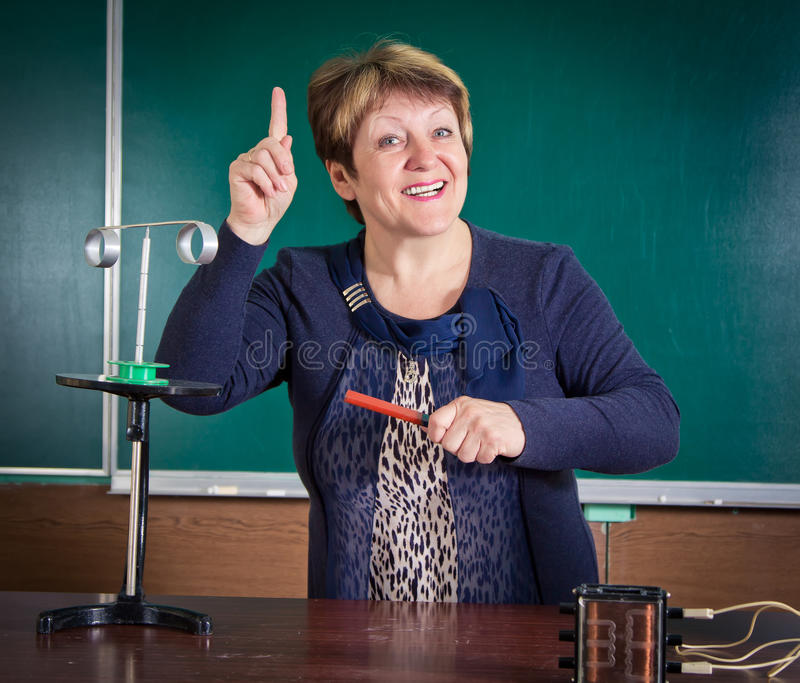 The teacher of physics explains concept of electromagnetic induction. Electrical engineering bases royalty free stock photo