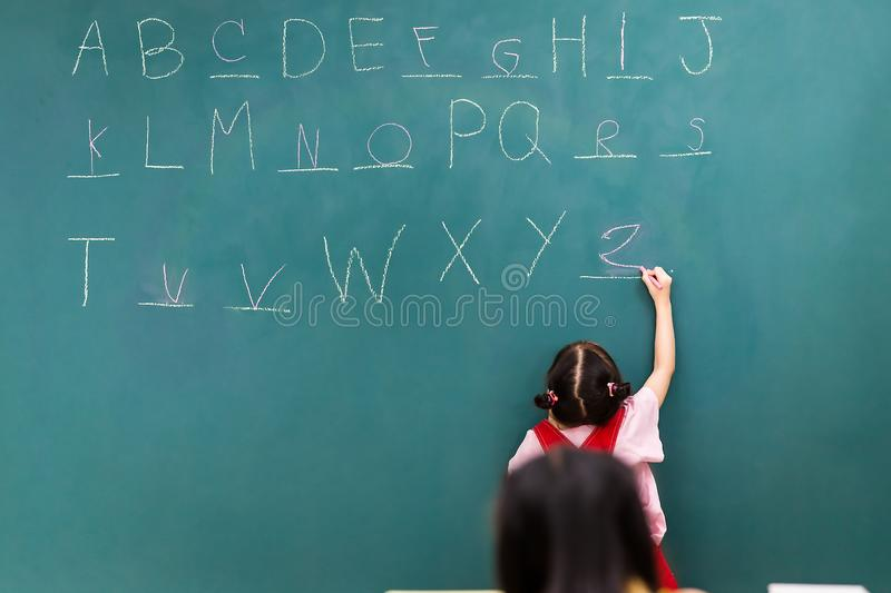 Teacher play fill in the blanks game with student. In Maths class, teacher writes fill in the blanks game on green board, to play with her students, girl writes royalty free stock photos
