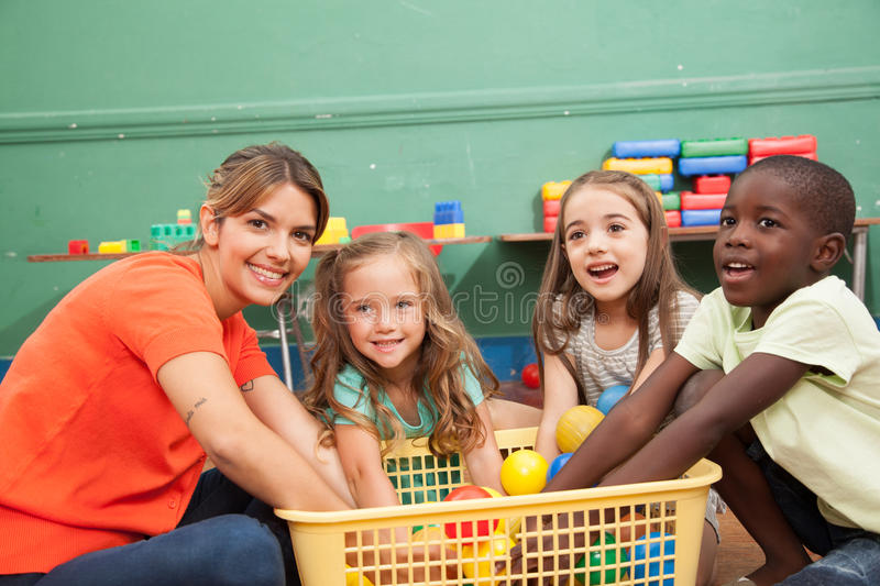 Teacher playing with her kindergarten class stock images