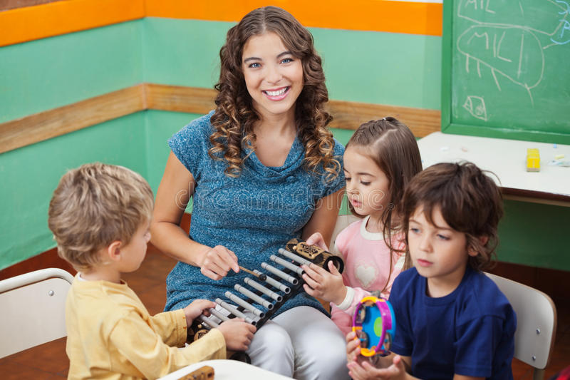 Teacher Playing Xylophone With Students In royalty free stock images