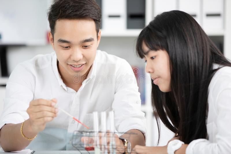 Teacher pouring chemical into test tube with his student . stock photos