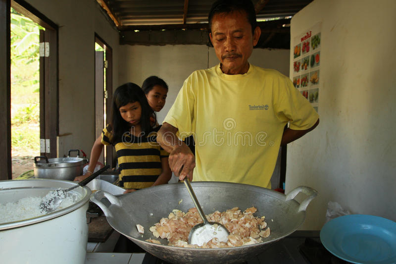 Teacher prepares a meal for deprived children stock photo