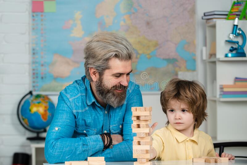 Teacher and pupil. Elementary school tutorship. School community partnership models. Happy father and focused son royalty free stock photography