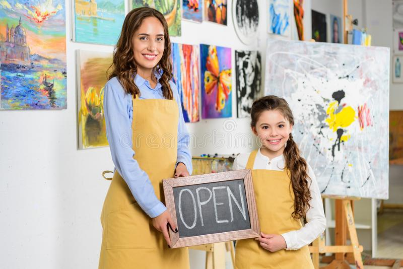teacher and pupil holding signboard with word open in workshop of stock photos