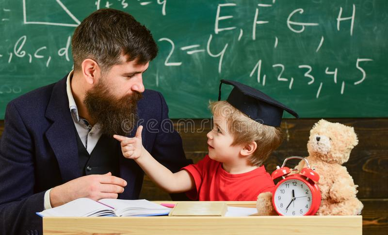 Teacher and pupil in mortarboard, chalkboard on background. Naughty child concept. Kid cheerful distracting while stock photos