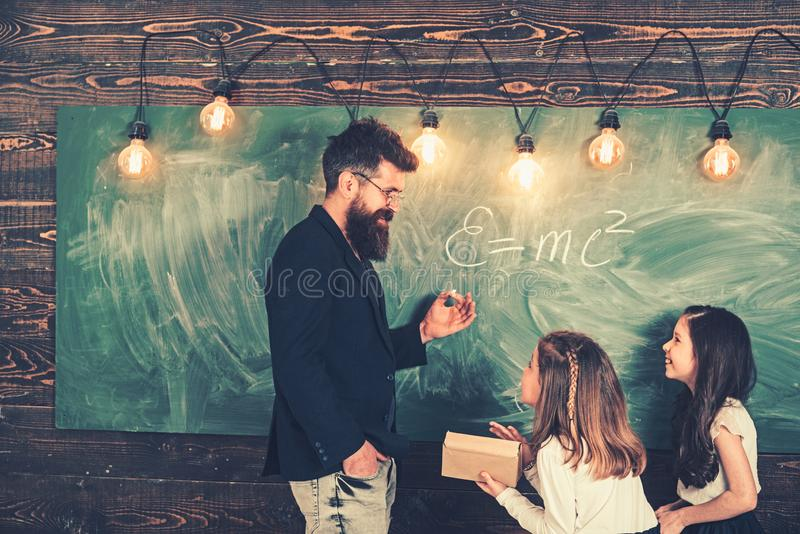 Teacher and pupils have lesson in class. Teacher write with chalk on chalkboard. Little girls listen to bearded man at royalty free stock photo