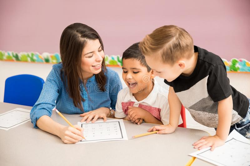 Teacher and pupils having fun at school. Good looking preschool teacher and students having a good time learning in the classroom royalty free stock image