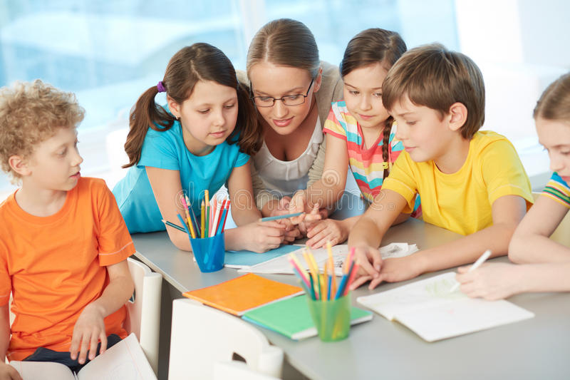 Teacher and pupils. Portrait of diligent schoolkids and their teacher interacting at lesson royalty free stock images