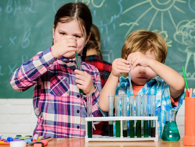 Teacher and pupils test tubes in classroom. Chemistry themed club. Discover and explore properties of substances stock images