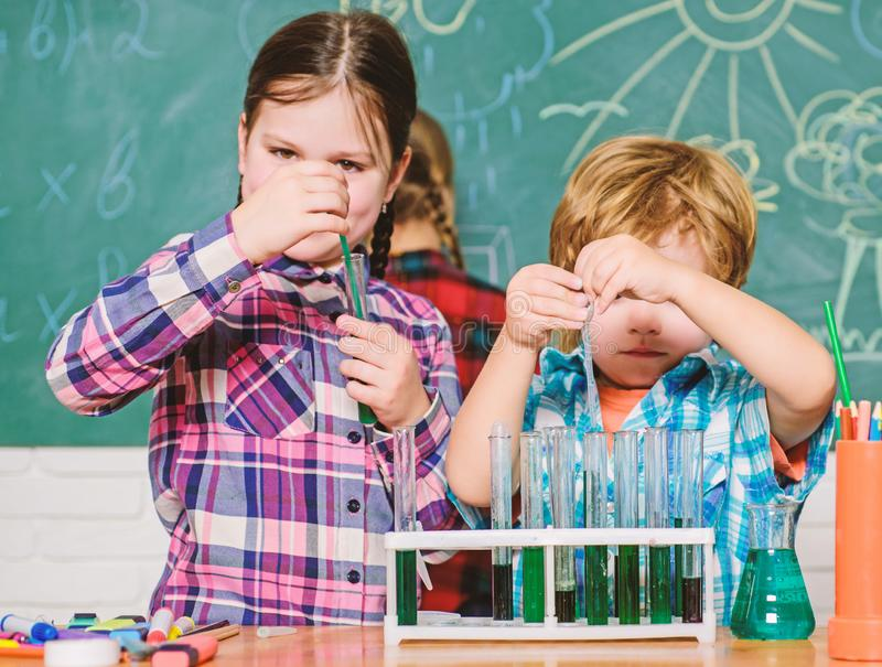 Teacher and pupils test tubes in classroom. Chemistry themed club. Discover and explore properties of substances royalty free stock image