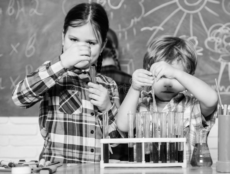 Teacher and pupils test tubes in classroom. Chemistry themed club. Discover and explore properties of substances royalty free stock images