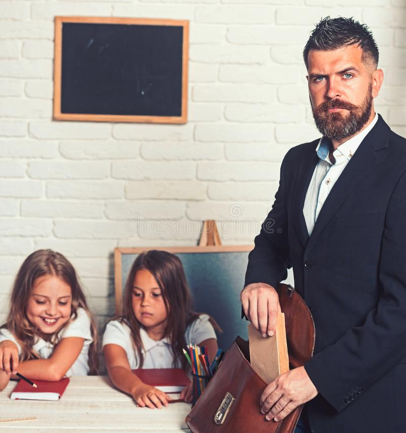 Teacher put book to a briefcase at class with kids. royalty free stock photos