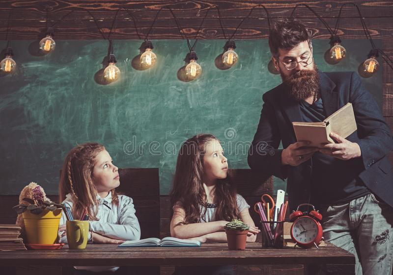 Teacher read book to pupils at lesson. Teacher teach schoolgirls in classroom. Bearded man and small girls in elementary stock image