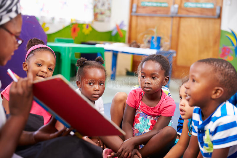 Teacher reading a book with a class of preschool children royalty free stock image