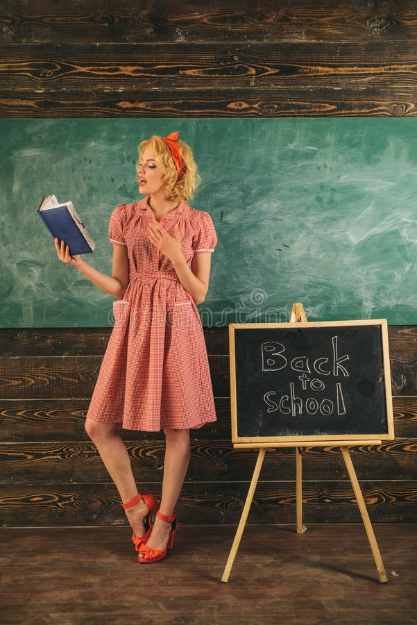 Teacher reading book in classroom. Pretty woman is back to school and reading book at blackboard. Adorable and genius stock image