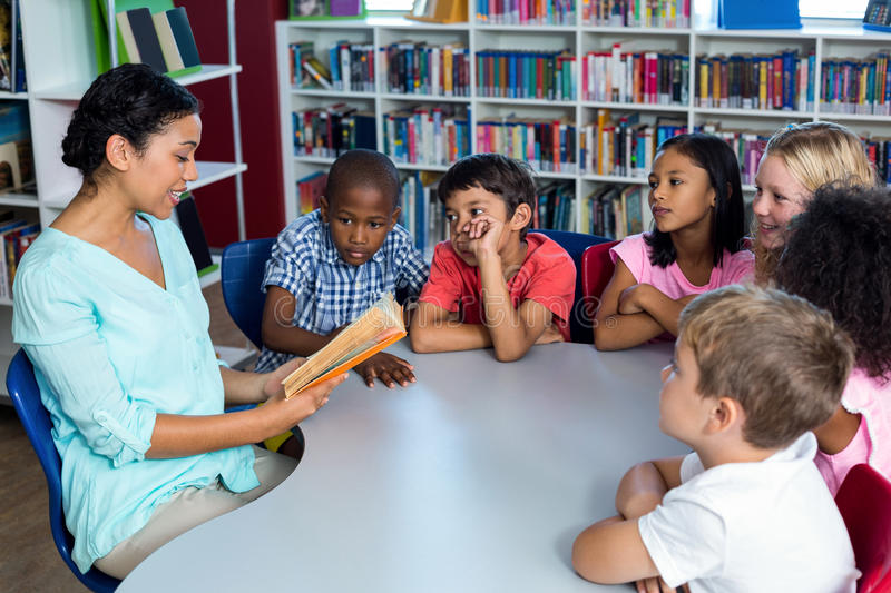 Teacher reading a book to children stock photo