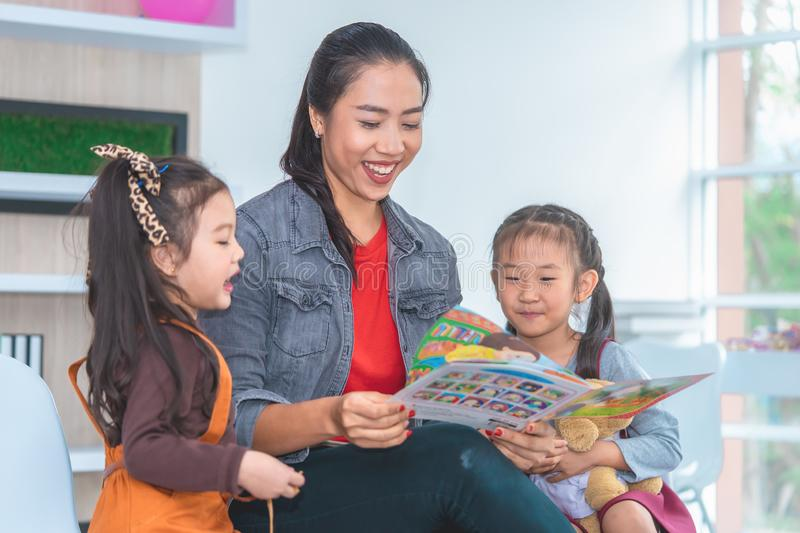 Teacher reading story book to kindergarten students laughing royalty free stock photo