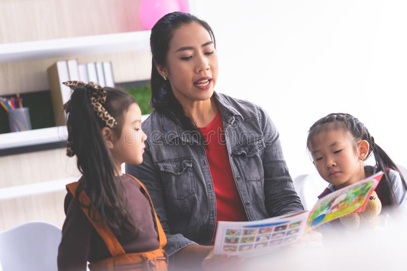 Teacher reading story book to kindergarten students stock photo