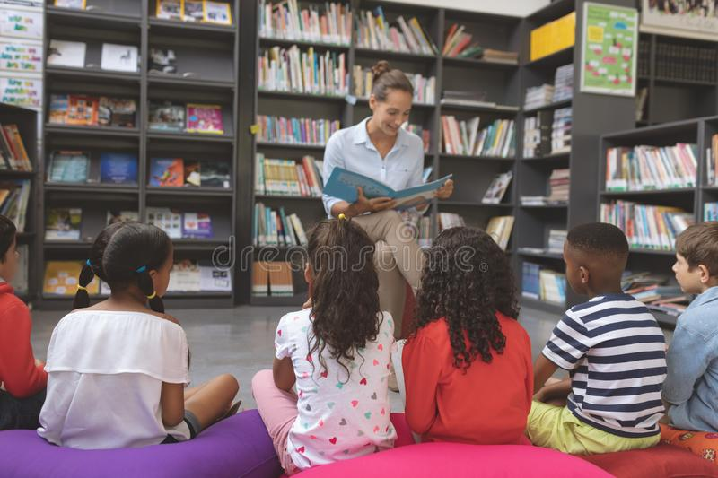 Teacher reading a story in a library to school kids sitting over big colored cushions. Front view of a teacher reading a story in a library to school kids royalty free stock photos