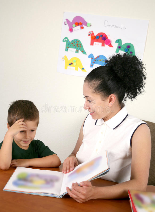 A Teacher Reads A Book With Her Preschool Student Royalty Free Stock Photo