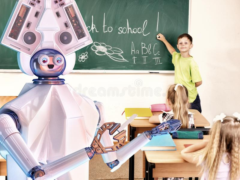 Teacher robot with school children in school class near blackboard. royalty free stock photo