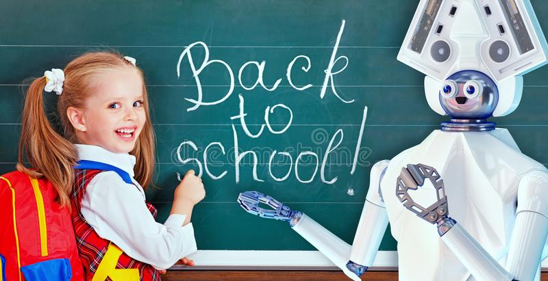 Teacher robot with schoolchild girl in school class near blackboard. stock photo