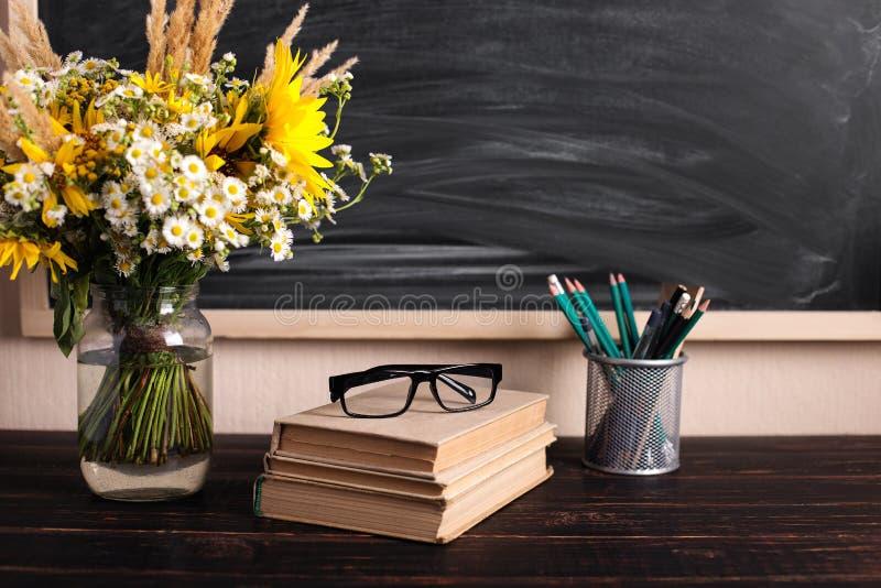 Teacher' s dagachtergrond Zwarte ruimte en verse wildflowers van het schoolbord lege exemplaar in vaas Vakantie vrouwelijke  stock afbeelding
