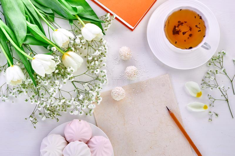Teacher`s Day, International Women`s Day, mother`s day. Cup of tea, bouquet of tulips and blank paper for drawing stock images