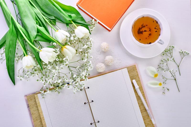 Teacher`s Day, March 8th, mother`s day. Cup of tea, bouquet of tulips and blank notebook for lectures stock photo