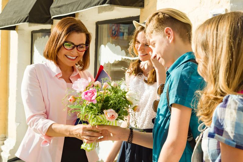 Teacher`s Day, outdoor portrait of happy middle aged female high school teacher with bouquet of flowers and group students. stock images