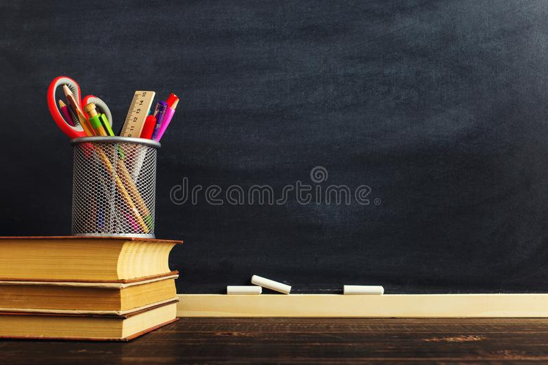 The teacher`s desk or a worker, on which the writing materials lie and books. Blank for text or background for a school theme. royalty free stock image