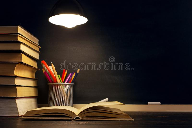 The teacher`s desk or a worker, on which the writing materials lie, a books, in the evening under the lamp. Blank for text or. Background for a school theme royalty free stock photos