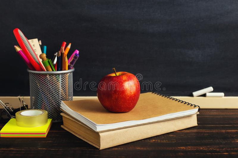 Teacher`s desk with writing materials, a book and an apple, a blank for text or a background for a school theme. Copy space stock images