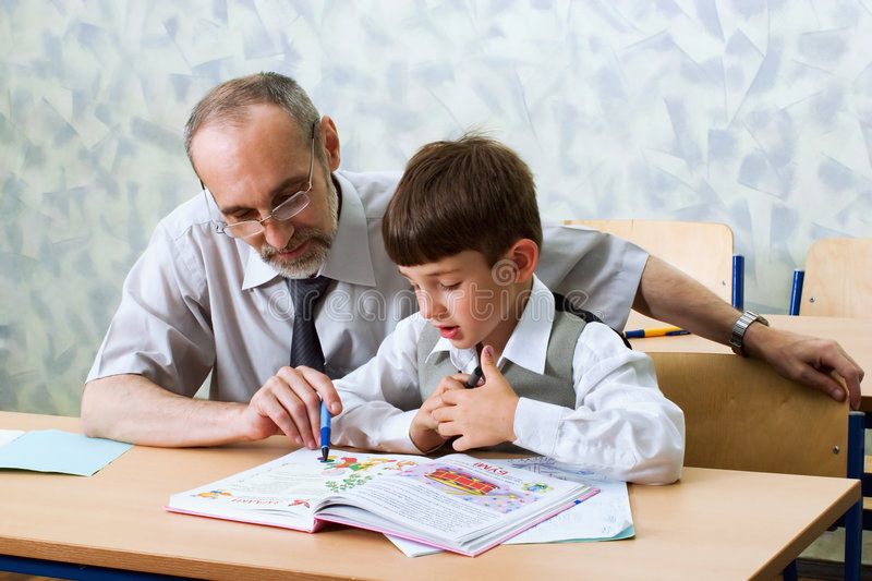Teacher and schooboy. Primary school. The teacher learns the boy to read royalty free stock photography