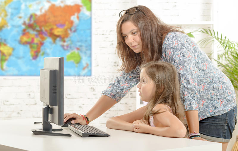 Teacher and a school girl with a computer royalty free stock images