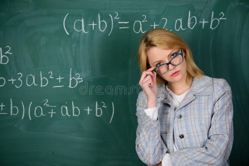 Teacher on school lesson at blackboard. woman in classroom. School. Home schooling. serious woman. Back to school. Teachers day. Study and education. Modern royalty free stock image