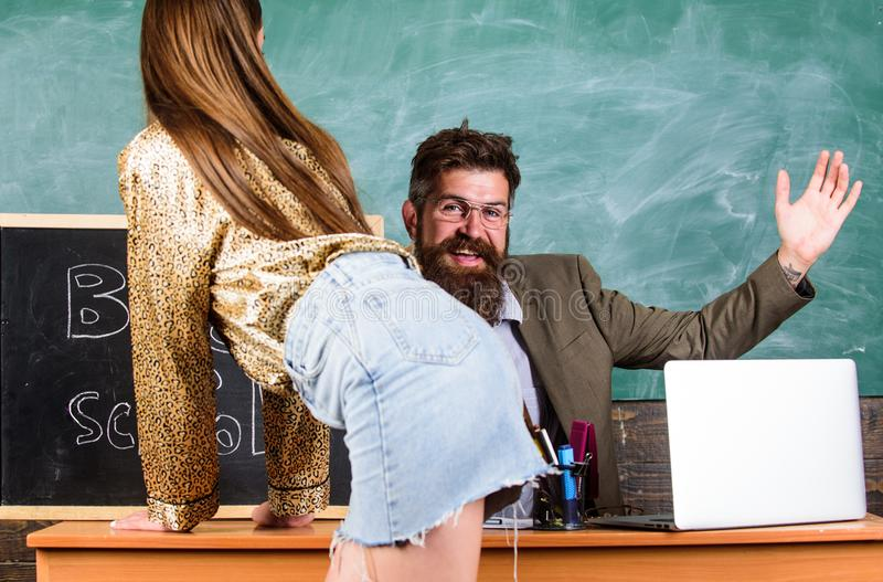 Teacher or school principal punishes slapping buttocks girl student. Student in mini skirt with buttocks waits royalty free stock photo