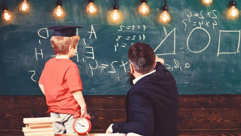 Teacher and schoolboy turned back in front of the green board. Kid in graduation cap learning shapes. Adult pointing at. Triangle drawn on the board royalty free stock photos