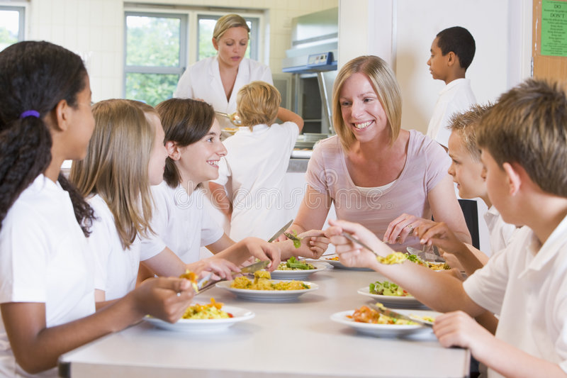 Teacher and schoolchildren enjoying their lunch stock image
