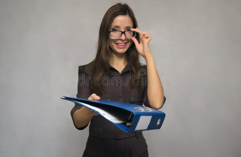 Teacher or secretary woman. Young beautiful secretary woman with long brown hair and dress holding in hands the documents folder. Teacher. Documentation work royalty free stock photo