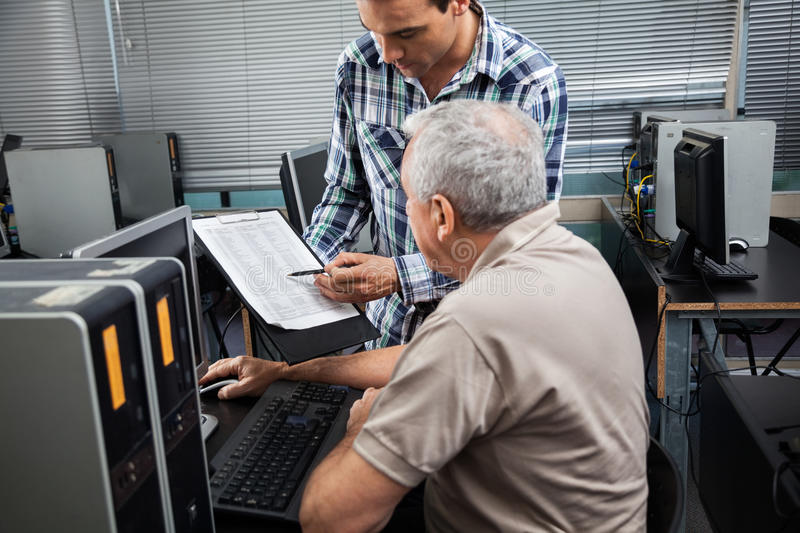 Teacher Showing Clipboard To Student In Computer Class royalty free stock photos