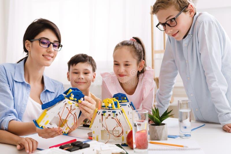 Teacher showing modern robot to children in classroom. Stem education. Teacher showing modern robot to children in classroom stock photos