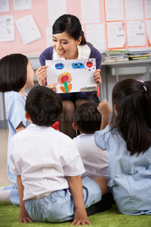 Teacher Showing Painting To Students. In Chinese School Classroom royalty free stock photos